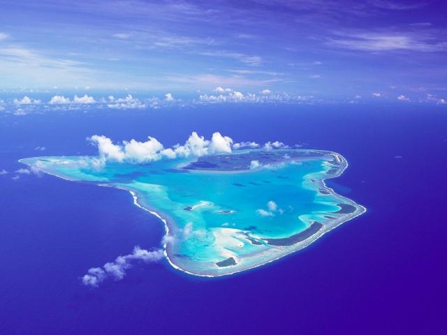 Birds eye view of Aitutaki on a clear blue day highlighting the islands crystal clear blue lagoon