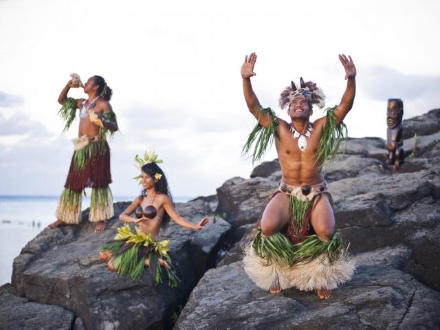 three Cook island cultural dancers performing at black rock location on Rarotonga