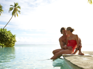 Image of a poolside romance, resort guests intimately relaxes on the edge of the swimming pool holding hands with their feet immersed in water
