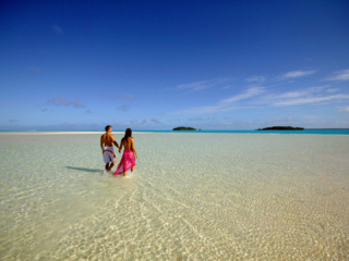 Image of a couple holding hands on One Foot Island featuring the clear white-stretched sand bank