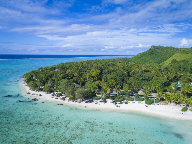 A stunning aerial image of the Ultimate Beachfront Bungalows and Villa categories, capturing a breath-taking view of the various shades of the blue lagoon