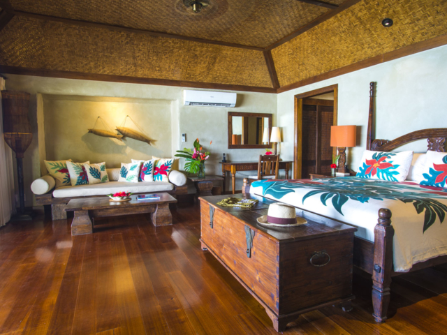 A side view of the Premium Beachfront Bungalow bedroom showcasing the attributes in the room and also features the beautiful cabana-bamboo-matting ceiling