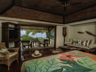 A beautiful interior image of the Premium Beachfront Bungalow bedroom overlooking the private balcony and the lagoon