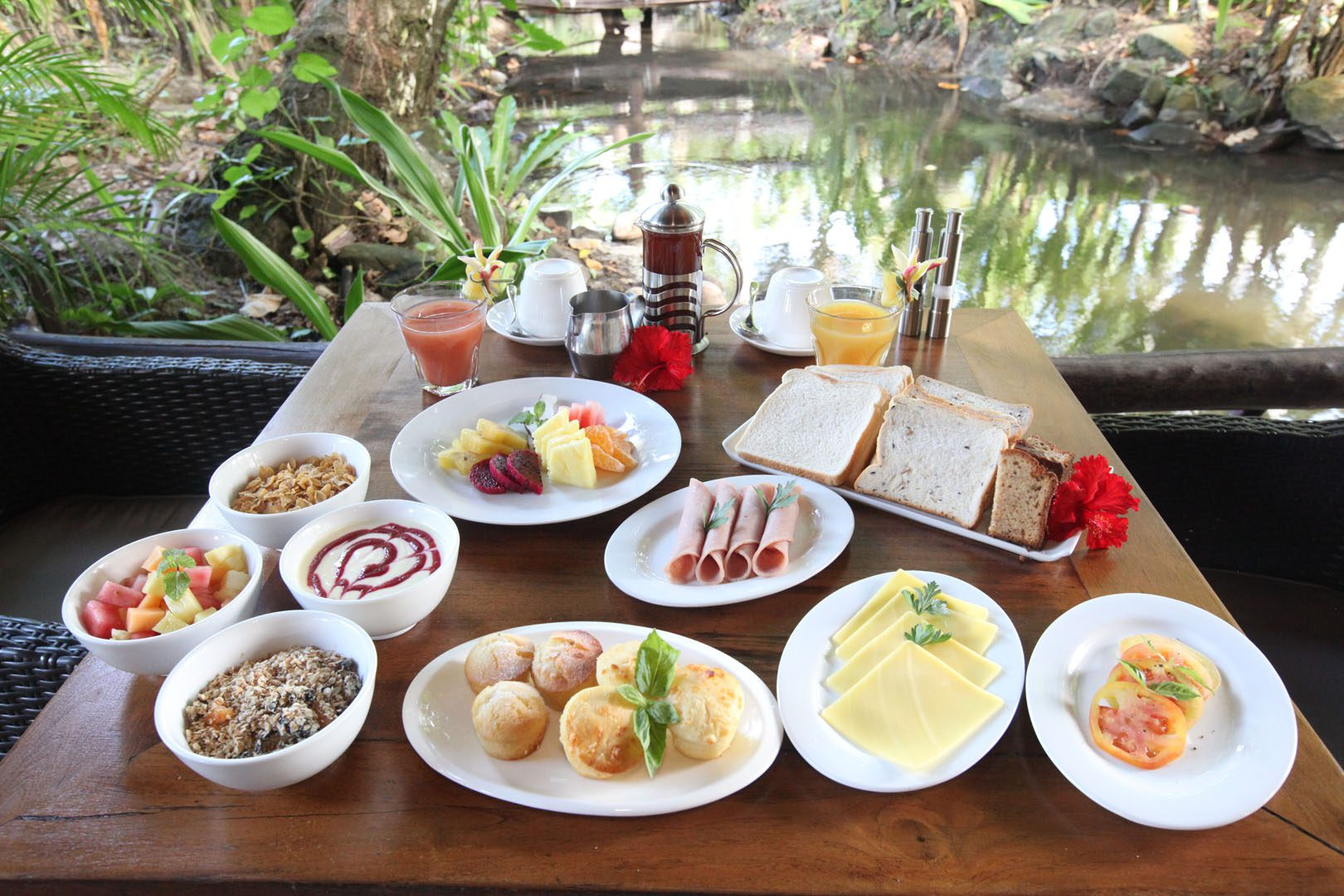 A delicious tropical continental breakfast selection set up featuring variety of breads, pastries, tropical fruits, ham and cheese along with a selection of coffee, tea and fruit juice