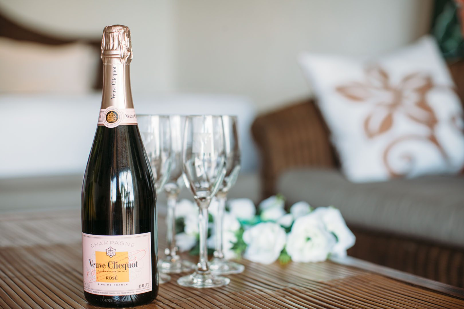 A bottle of champagne placed on a table with four glasses and white roses in the background as a sign of celebration