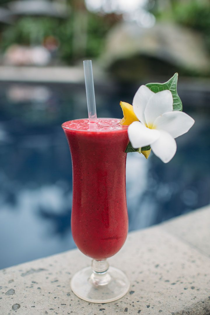 A thirst-quenching image of a beautiful tropical fruit cocktail garnished with frangipani and a slice of fruit