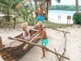 Children of Resort guests playing in the Warrior Canoe by the beach