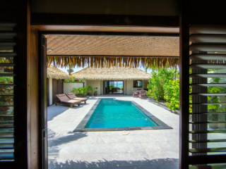View from the inside of the Ultimate beachfront villa, leading out to the pool area with a lagoon view