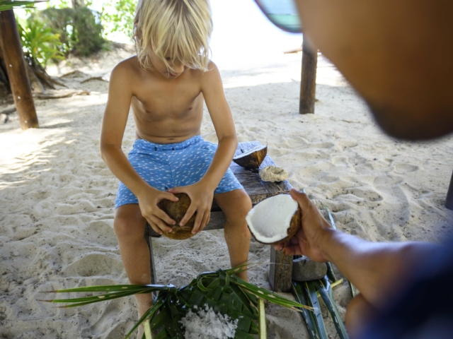 Supervised coconut grating by the beach, performed by a young boy with the help of the Resort Attendant
