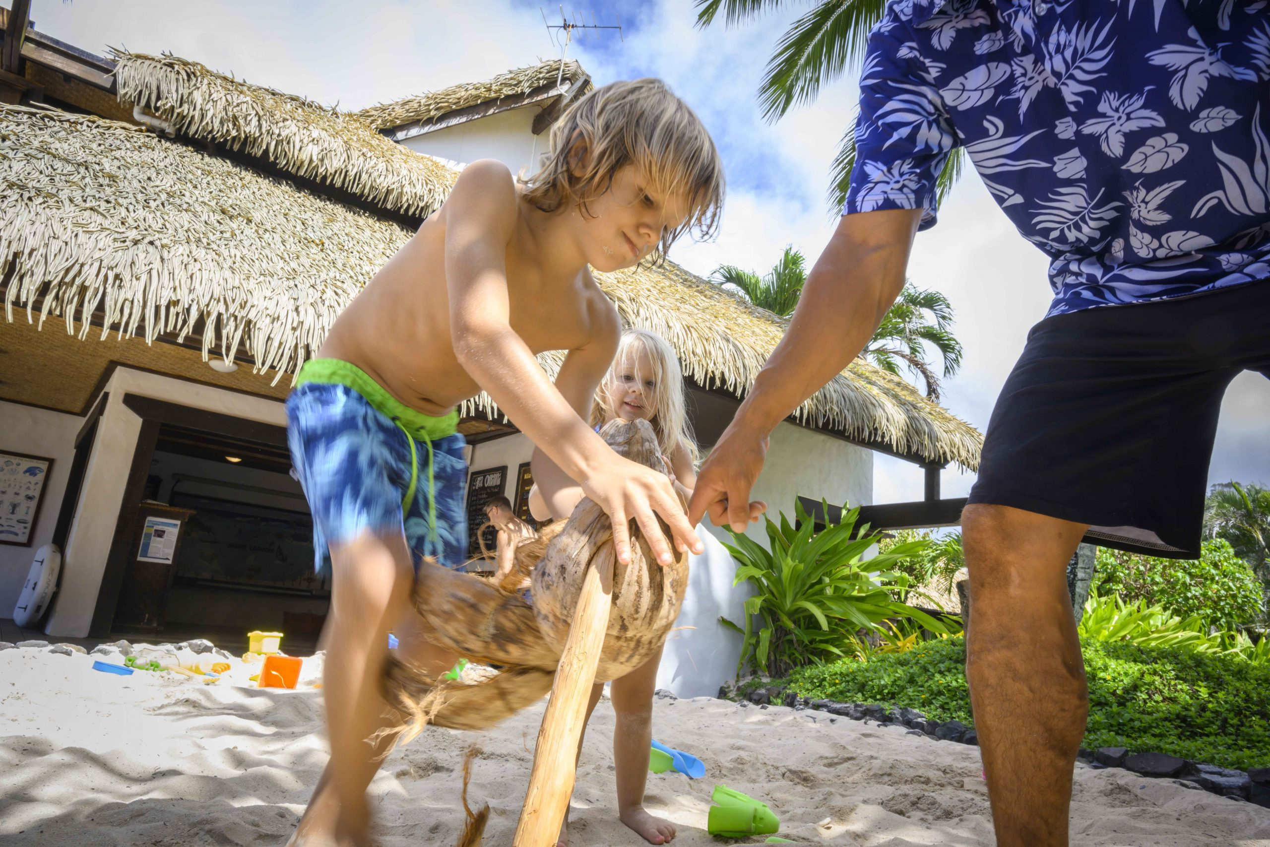 A supervised coconut husking performed by a young boy with the help of the Resort Attendant