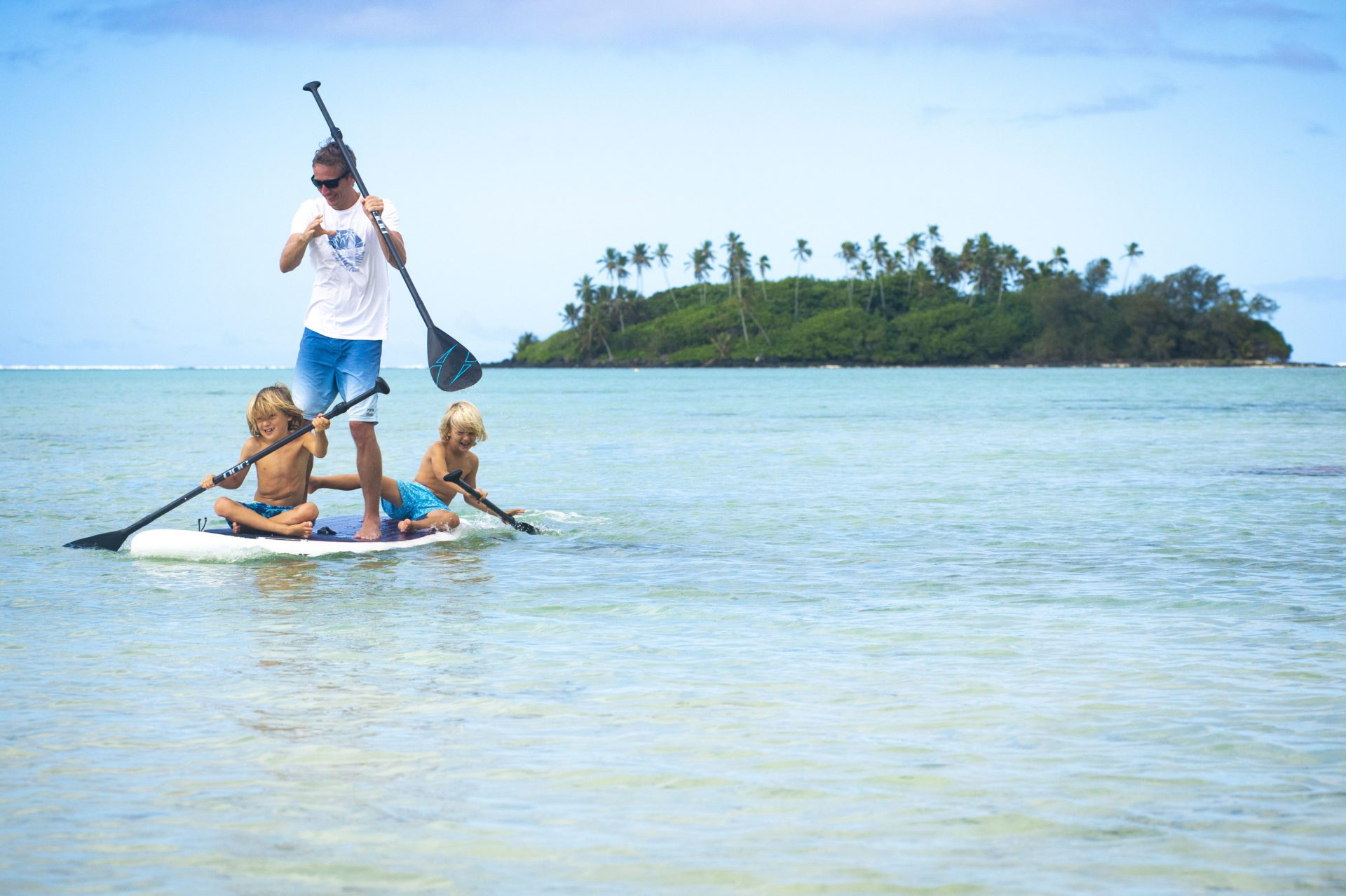 A beautiful image of father and two sons bonding in the lagoon sharing a stand-up paddleboard and smilingly paddles through the waters of Muri