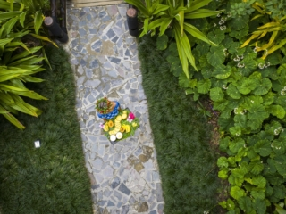 Aerial image of a restaurant attendant walks on a smooth pathway along the lush garden, holding a tropical garden fruit platter garnished with beautiful seasonal flowers