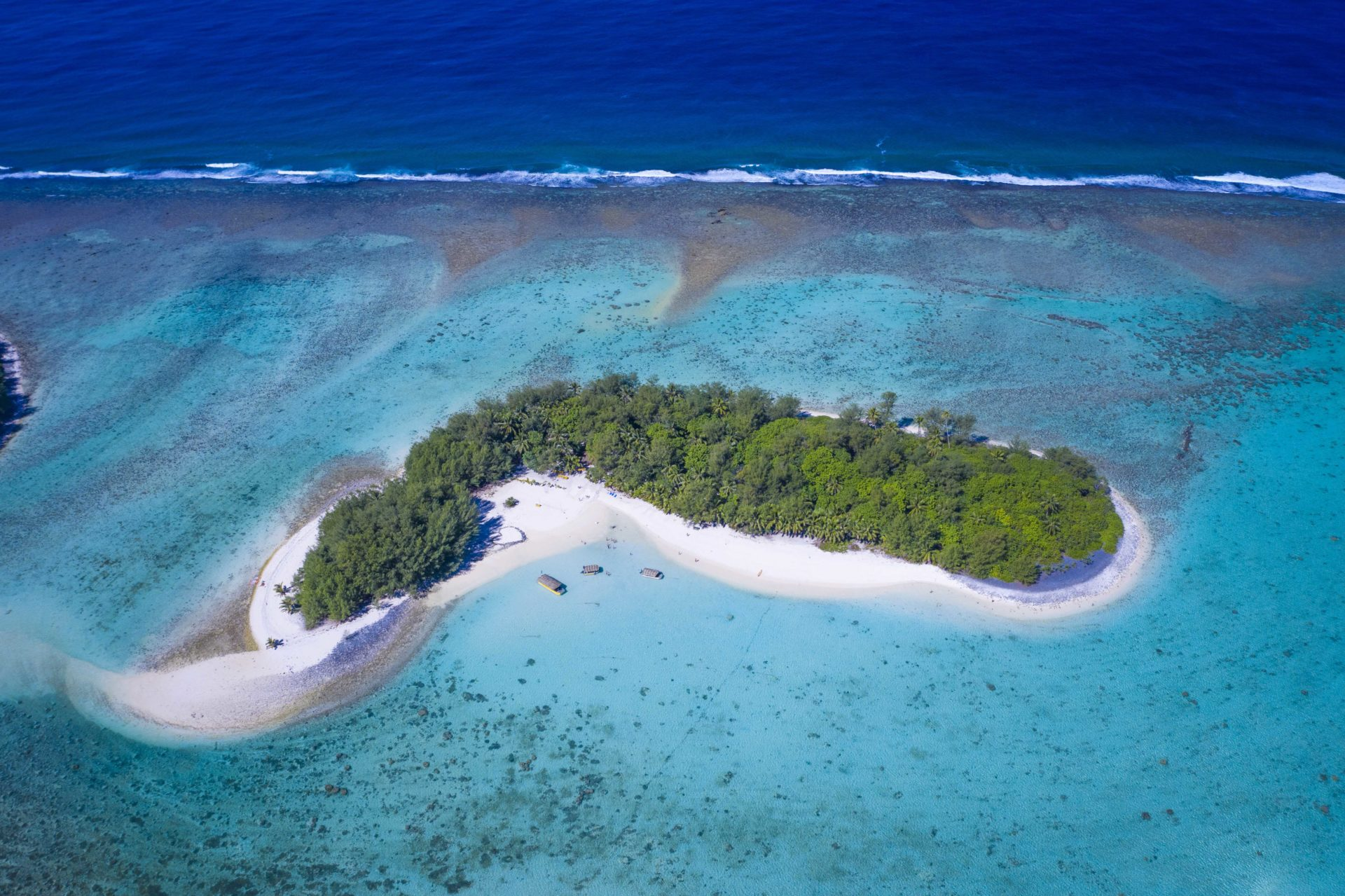 A spectacular aerial image of Motu Koromiri, a secluded private island set amidst the clear blue lagoon showcasing the splashing of waves towards the outer reef