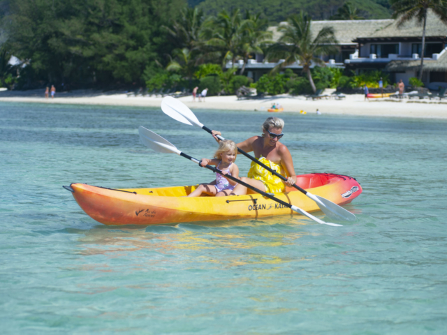 Image of mother and daughter happily kayaking in the Muri Lagoon, in front of the resort