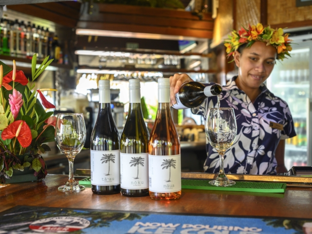 Resort bar attendant showcasing her wine-pouring skills and the variety of wine options available at the bar