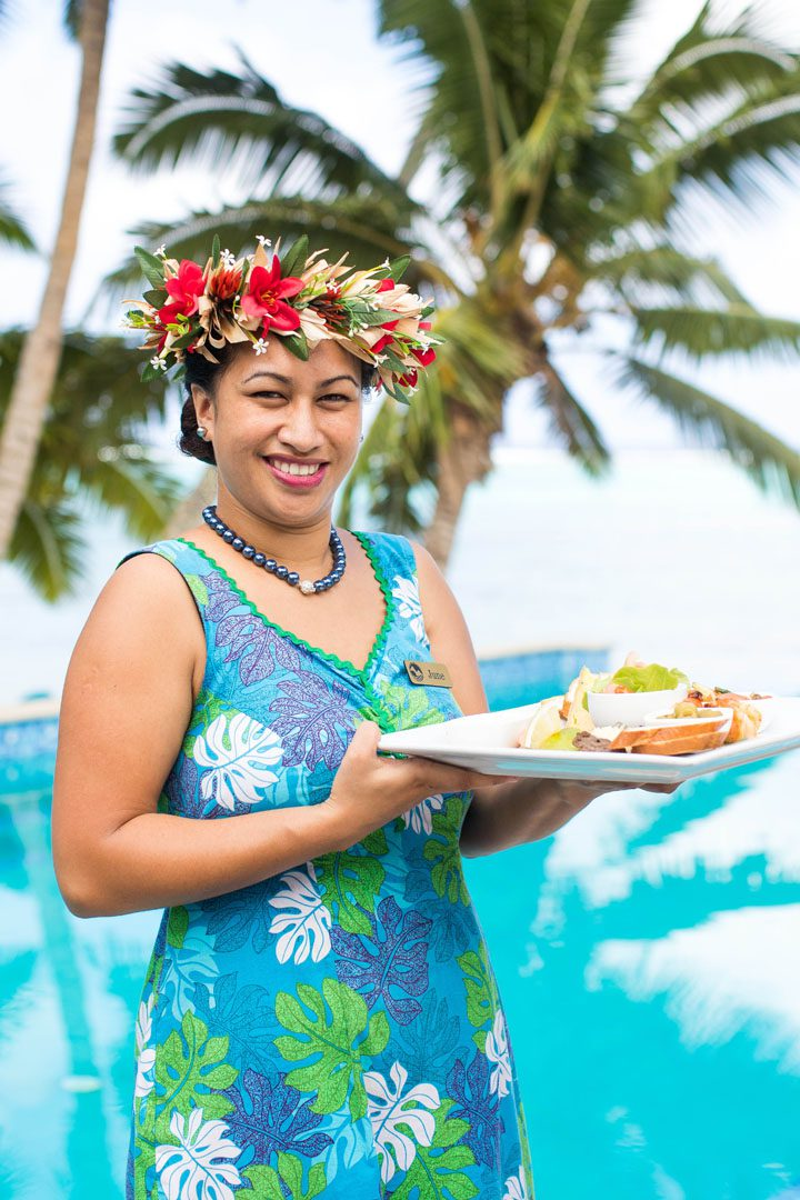Friendly Waitress serving a tropical platter overlooking our infinity pool