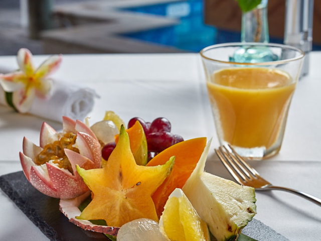 A colourful fresh fruit platter and glass of juice in a garden setting
