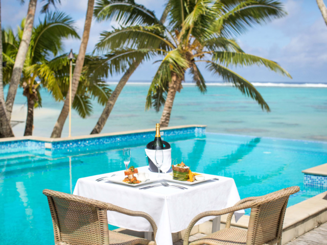 A restaurant table with tropical meals next to infinity pool and beach on a sunny day